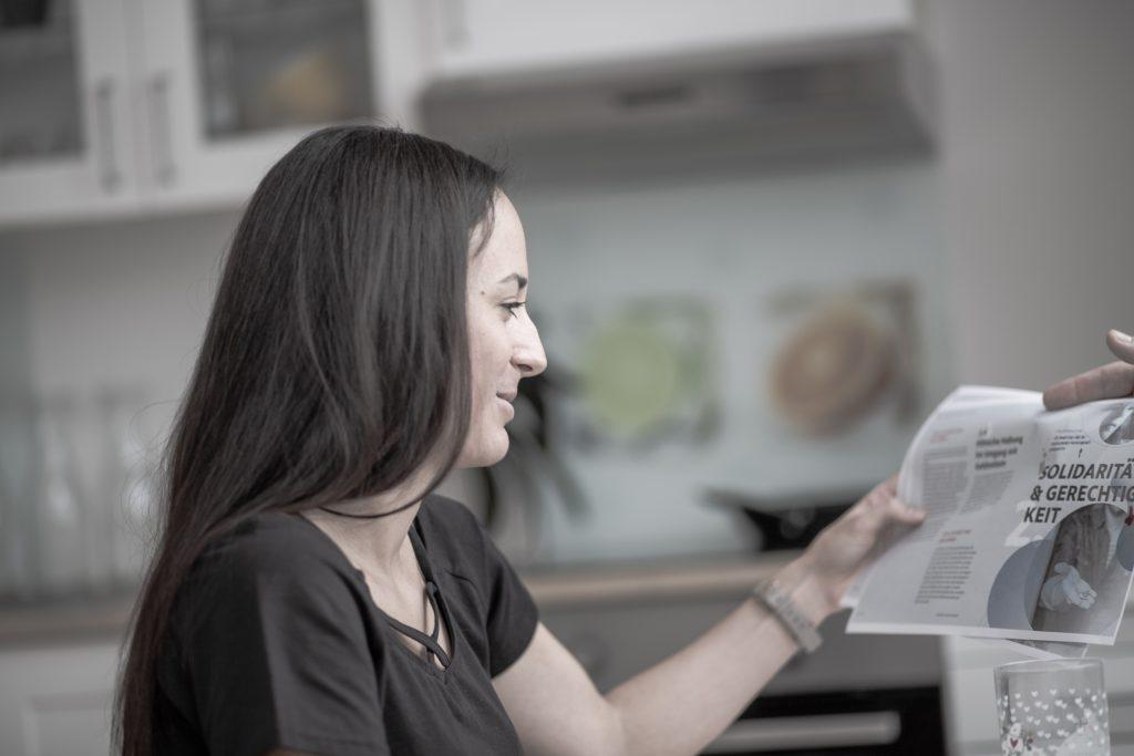 Frau mit dunklen Haaren liest einen Bericht und lächelt dabei
